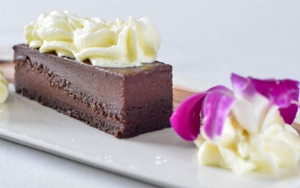 chocolate fudge cake with whipped cream and edible flower at Pescada Dairy