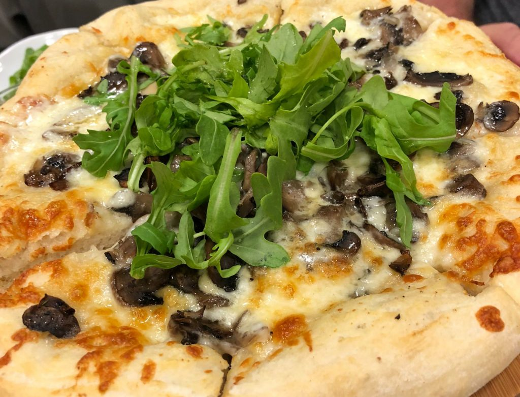 mushroom cheese pizza with arugula greens ontop at the Bay Cafe in Brooklyn