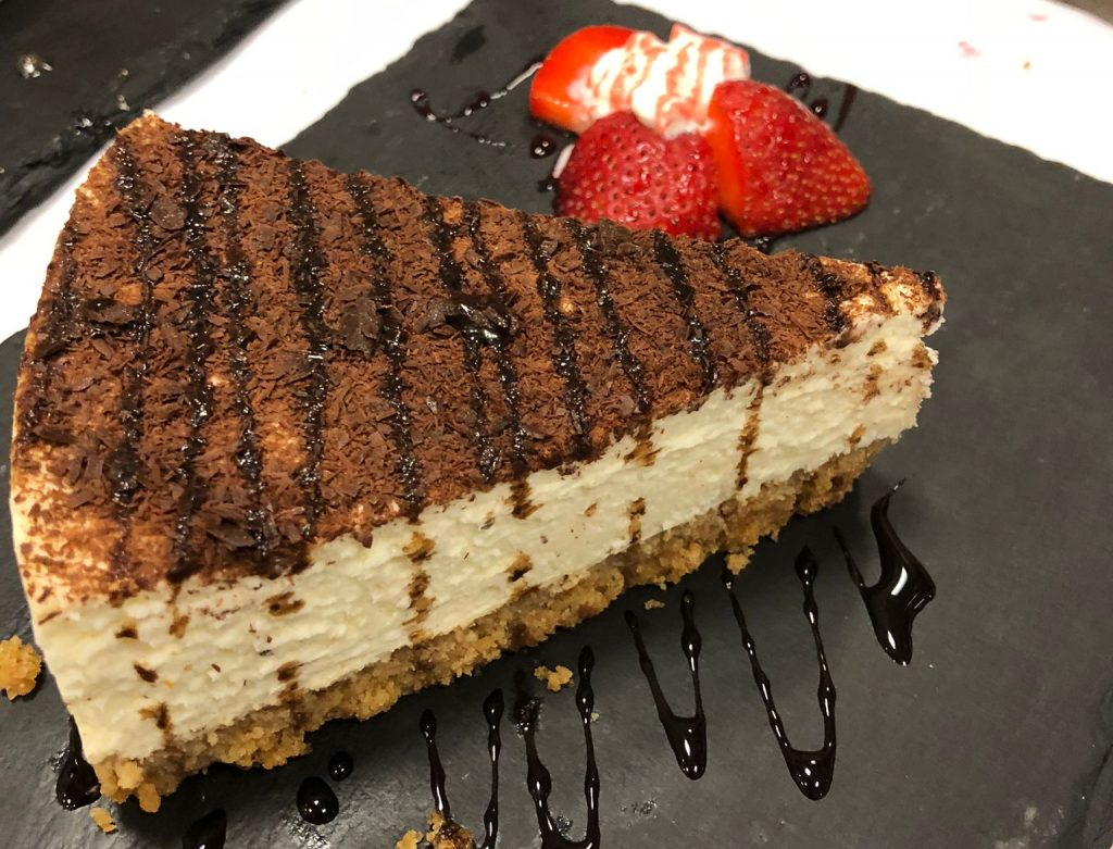 new york style cheesecake with chocolate sauce and strawberries