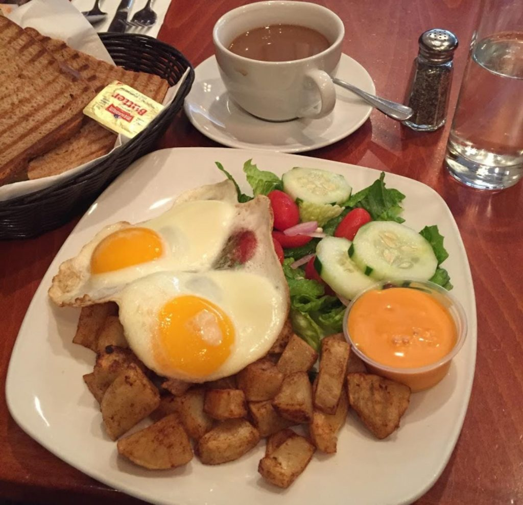 sunny side up eggs, potato fries, salad, toast, butter, coffee at spoons of Boro Park
