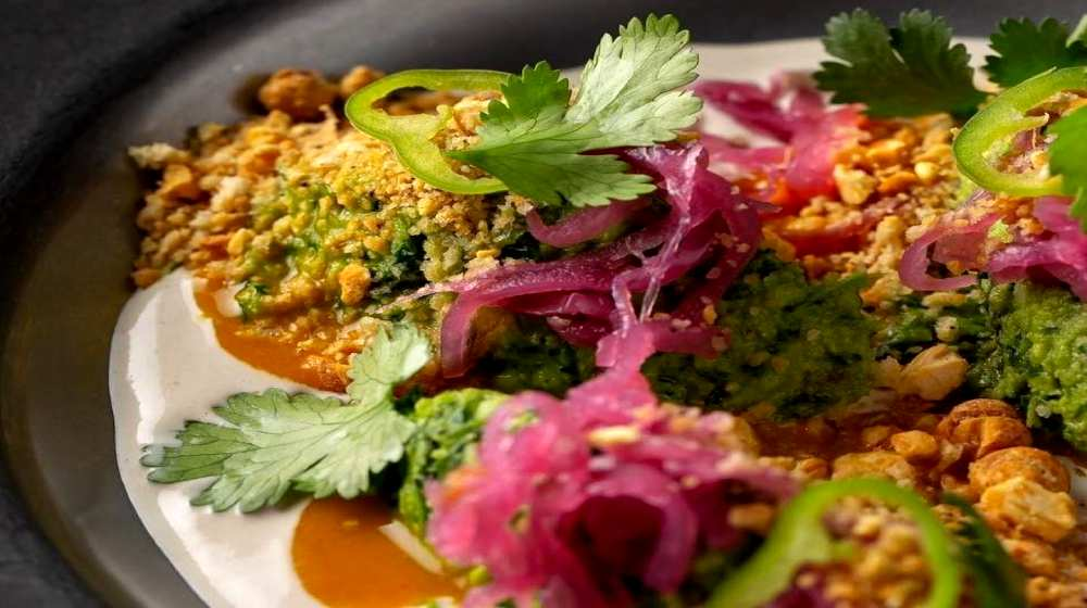 deconstructed falafel, chickpea crumble, herbs and pickled onions in tahini sauce