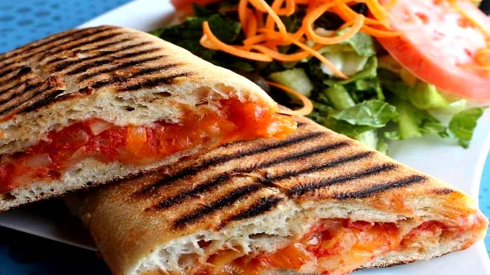 tomato panini with fresh shredded carrot salad on the side